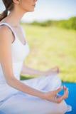 Mujer joven pacífica que se sienta en la posición de la yoga respecto a su estera Fotografía de archivo