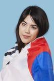 Mujer joven patriótica envuelta en bandera coreana sobre fondo azul Foto de archivo