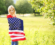 Mujer joven patriótica hermosa con la bandera americana Imagenes de archivo