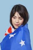 Mujer joven patriótica envuelta en bandera australiana sobre fondo azul Imagen de archivo