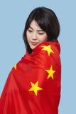 Mujer joven patriótica envuelta en bandera china sobre fondo azul Fotografía de archivo