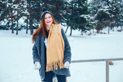 Mujer joven pelirroja con una bufanda roja en un bosque del invierno Foto de archivo libre de regalías