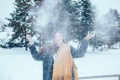 Mujer joven pelirroja con una bufanda roja en un bosque del invierno Imagenes de archivo
