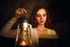 Mujer joven pelirroja hermosa con el libro de lectura de la lámpara de keroseno Fotos de archivo