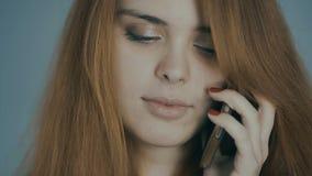 Mujer joven pelirroja que habla en el teléfono y que sonríe en el fondo del estudio, emociones del concepto, comunicación, tecnol