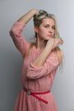 Mujer joven, pelo largo rubio de fascinación de la muchacha en fondo gris Foto de archivo