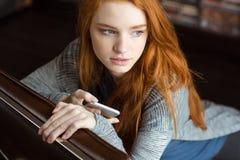 Mujer joven pensativa atractiva que sienta y que sostiene el teléfono móvil Imagenes de archivo
