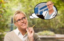 Mujer joven pensativa con el lápiz y ella misma como enfermera o Docto Foto de archivo libre de regalías