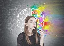 Mujer joven pensativa con la pluma, cerebro imagen de archivo libre de regalías