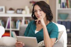 Mujer joven pensativa con la tableta Foto de archivo