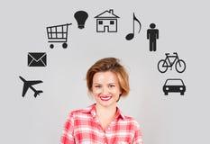 Mujer joven pensativa con los iconos de las multimedias alrededor de su cabeza Imágenes de archivo libres de regalías