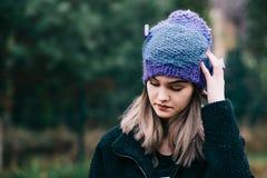 Mujer joven pensativa en casquillo azul violeta de lana Fotos de archivo libres de regalías