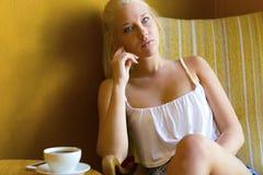 Mujer joven pensativa en el café con café y smartphone Imagen de archivo libre de regalías
