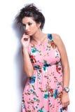 Mujer joven pensativa en el vestido de flores que mira lejos fotos de archivo