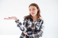 Mujer joven pensativa en la camisa de tela escocesa que lleva a cabo el copyspace en la palma Imagen de archivo
