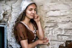Mujer joven pensativa en un vestido rústico que se coloca cerca de la pared de ladrillo vieja en la vieja sensación de la casa so imagenes de archivo