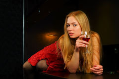 Mujer joven pensativa en una barra. Fotografía de archivo