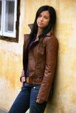 Mujer joven pensativa en una pared de la casa foto de archivo