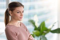 Mujer joven pensativa pensativa que mira a través de la ventana, CRO (coordinadora) de los brazos Fotos de archivo