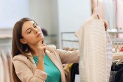 Mujer joven pensativa que elige la ropa en alameda Foto de archivo libre de regalías