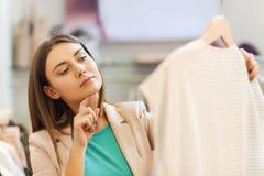 Mujer joven pensativa que elige la ropa en alameda Imagen de archivo