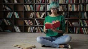 Mujer joven pensativa que goza leyendo un libro almacen de metraje de vídeo