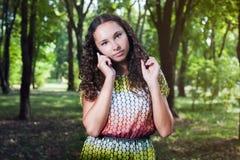 Mujer joven pensativa que habla al aire libre móvil Fotografía de archivo