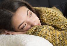 Mujer joven pensativa que miente en el sofá Foto de archivo libre de regalías