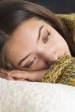 Mujer joven pensativa que miente en el sofá Fotografía de archivo libre de regalías