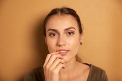 Mujer joven pensativa que presenta para la cámara Imagen de archivo libre de regalías
