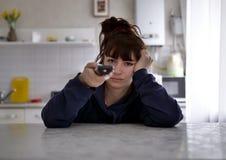 Mujer joven pensativa que se sienta con teledirigido en un fondo borroso de la cocina imagenes de archivo