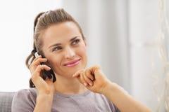 Mujer joven pensativa que se sienta en el sofá y el teléfono móvil que habla Imagen de archivo