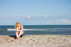 Mujer joven pensativa que se sienta en la playa imagen de archivo libre de regalías