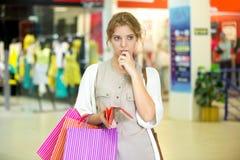 Mujer joven pensativa que sostiene la cartera vacía después de hacer compras Imágenes de archivo libres de regalías