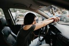 Mujer joven pensativa y triste con los brazos en el volante del coche en un día lluvioso imagen de archivo
