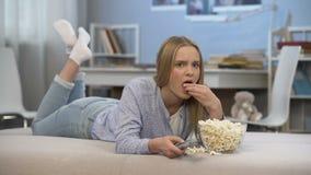 Mujer joven perezosa que pierde tiempo delante de la televisión casera, canales cambiantes almacen de video