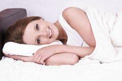 Mujer joven a permanecer en cama fotografía de archivo
