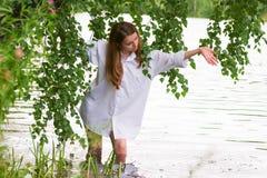 Mujer joven por el lago. Foto de archivo