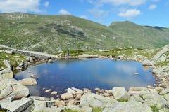 Mujer joven por un lago azul tranquilo de la montaña Imagenes de archivo