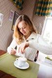 Mujer joven positiva con café de la taza en café Fotos de archivo