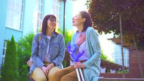 Mujer joven positiva con lesión en las muletas que se sientan en un banco en el parque y que se divierten con un amigo almacen de video