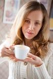 Mujer joven positiva con una taza de café en manos Imagen de archivo