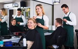 Mujer joven positiva que corta el pelo femenino del pensionista Imagen de archivo