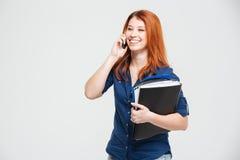Mujer joven preciosa alegre con las carpetas que habla en el teléfono celular Imagen de archivo