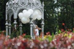 Mujer joven preciosa con los globos en el parque imágenes de archivo libres de regalías