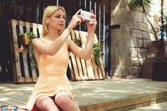 Mujer joven preciosa en la opinión urbana de fotografía del vestido con la cámara del teléfono móvil durante viaje del verano Fotografía de archivo libre de regalías