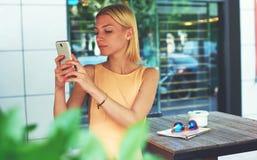 Mujer joven preciosa en la opinión urbana de fotografía del vestido con la cámara del teléfono móvil durante viaje del verano Imagenes de archivo