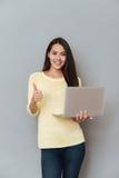 Mujer joven preciosa feliz que sostiene el ordenador portátil y que muestra los pulgares para arriba imágenes de archivo libres de regalías