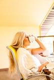 Mujer joven preciosa que bebe su café de la mañana, sentándose en la silla y mirando hacia fuera la ventana Mañana y el despertar Imagen de archivo