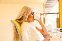 Mujer joven preciosa que bebe su café de la mañana, sentándose en la silla y mirando hacia fuera la ventana Mañana y el despertar Imágenes de archivo libres de regalías